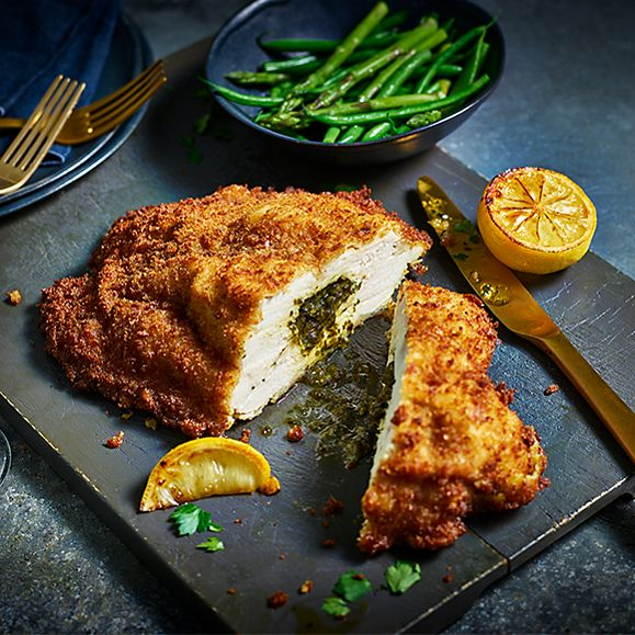 A plate with Our Best Ever chicken Kiev sliced in two