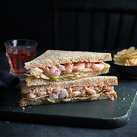 Our Best Ever prawn sandwich on a chopping board with crisps and a drink