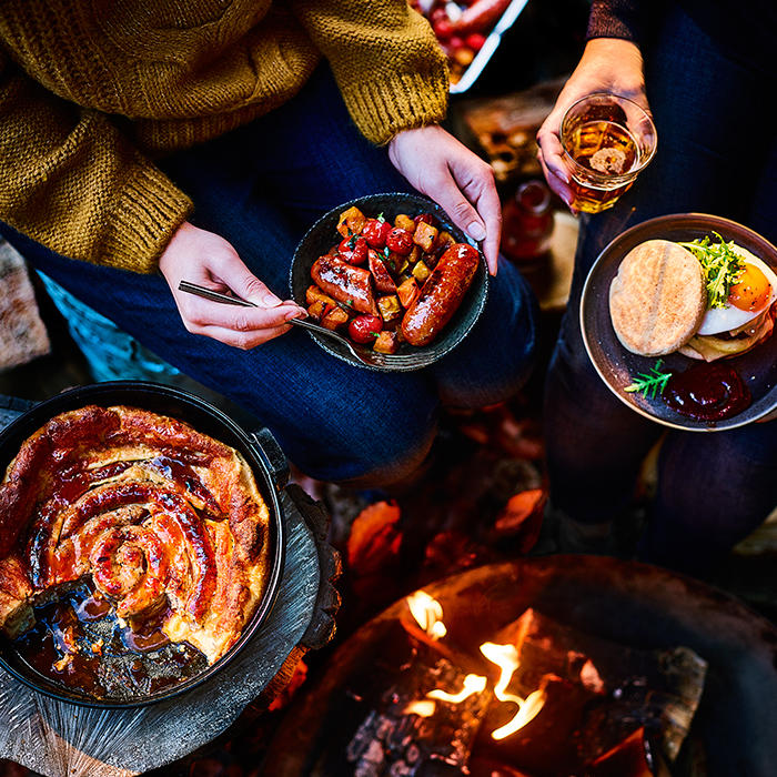 Selection of sausage dishes around a bonfire
