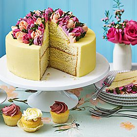 Cream sponge cake with pink and purple flowers on top