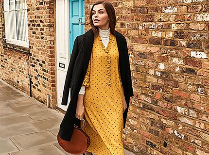 Woman wearing yellow dress layered over cream roll neck and black boots