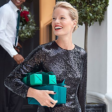 Woman wearing a black sequin dress carries Christmas gifts