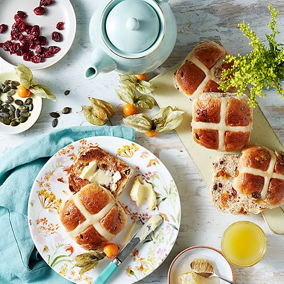 Golden Hot Cross buns with butter, tea and dried fruits