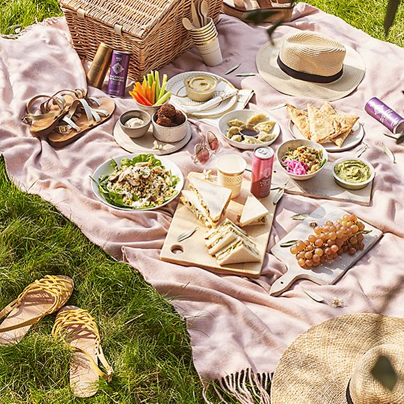 A picnic spread on a pink blanket in the park
