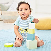 Baby boy playing with building blocks wearing an M&S outfit