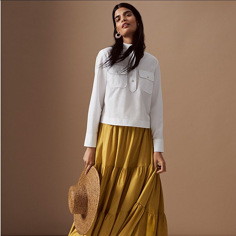 Woman wearing white shirt and mustard-yellow maxi skirt