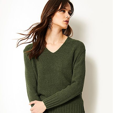 Woman wearing an olive green V-neck jumper