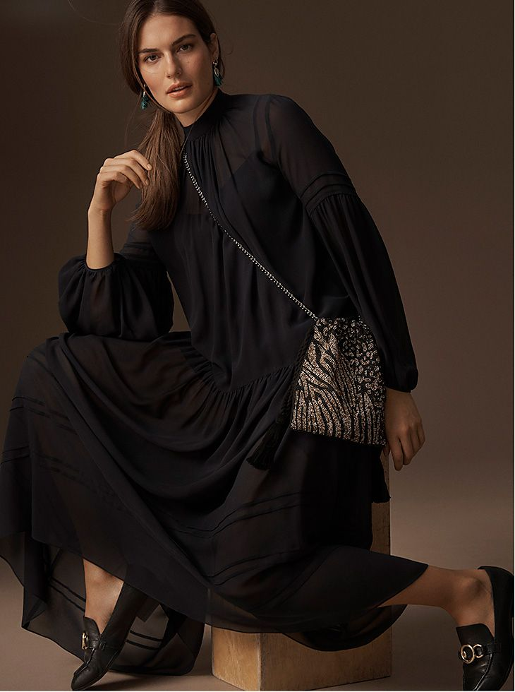 Model wears a long black chiffon dress with a beaded evening bag and black buckled loafers