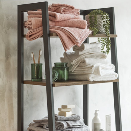 Towels, bathroom accessories and artificial plant on shelving
