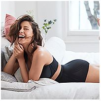 Woman lying on a bed wearing a black bra and black firm control waist & thigh Sculpt™ no VPL cincher