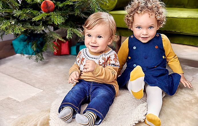 Baby girl and baby boy wearing M&S Christmas jumper, jeans and denim dress