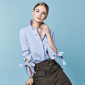 Model wears blue chambray shirt with bow sleeves and high-waisted skirt