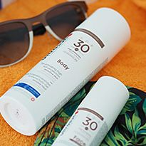 Ultrasun sun creams next to a pair of sunglasses