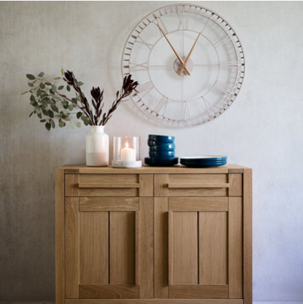 Sonoma wooden sideboard in a hallway with a vase, candle, plates and a wall clock