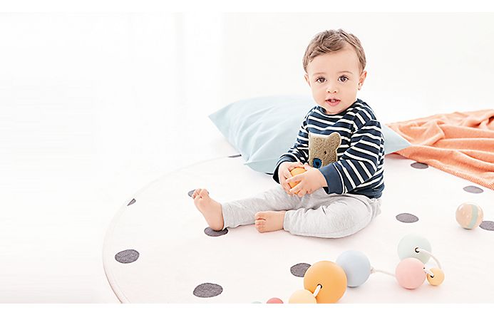Baby sat on a playing mat wearing a striped teddy bear jumper and grey trousers