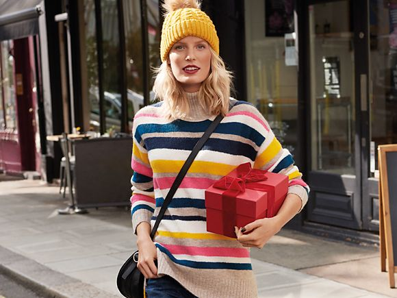 Woman wears a yellow bobble hat and striped jumper