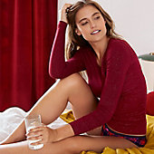 Woman sat on a bed wears a red long-sleeve thermal top