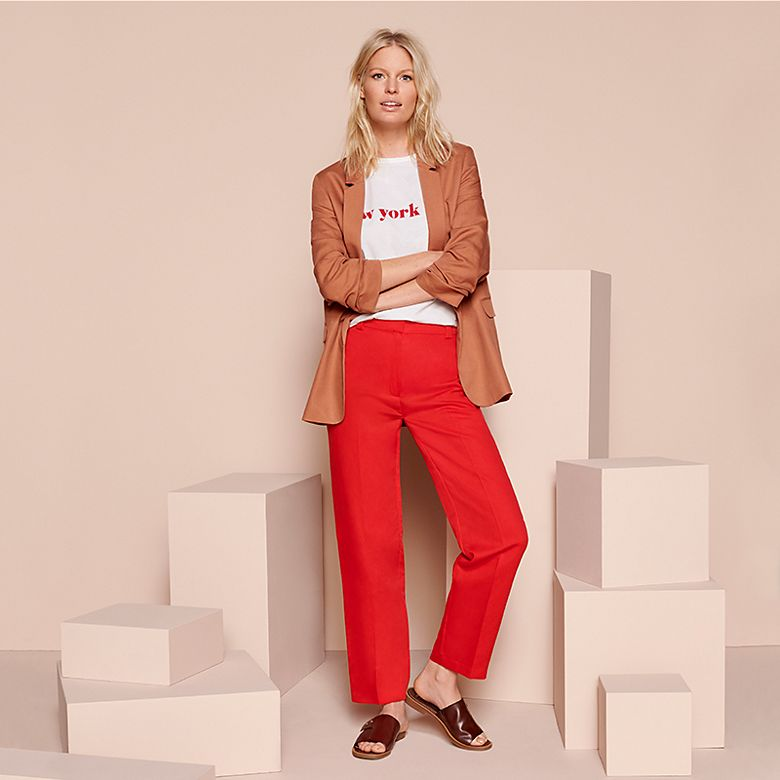 Woman wearing tobacco-brown blazer, slogan T-shirt and red trouser