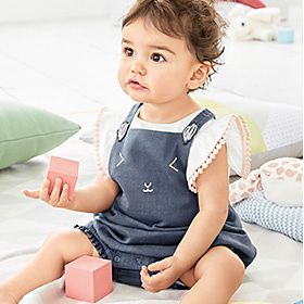 Baby girl holding a building block wearing a pompom-embroidered top and mouse face denim romper