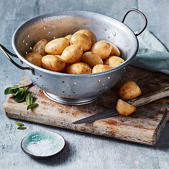 A colander of Jersey Royal potatoes with a knife, mint and salt