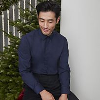 Man wearing a navy shirt in front of a Christmas tree