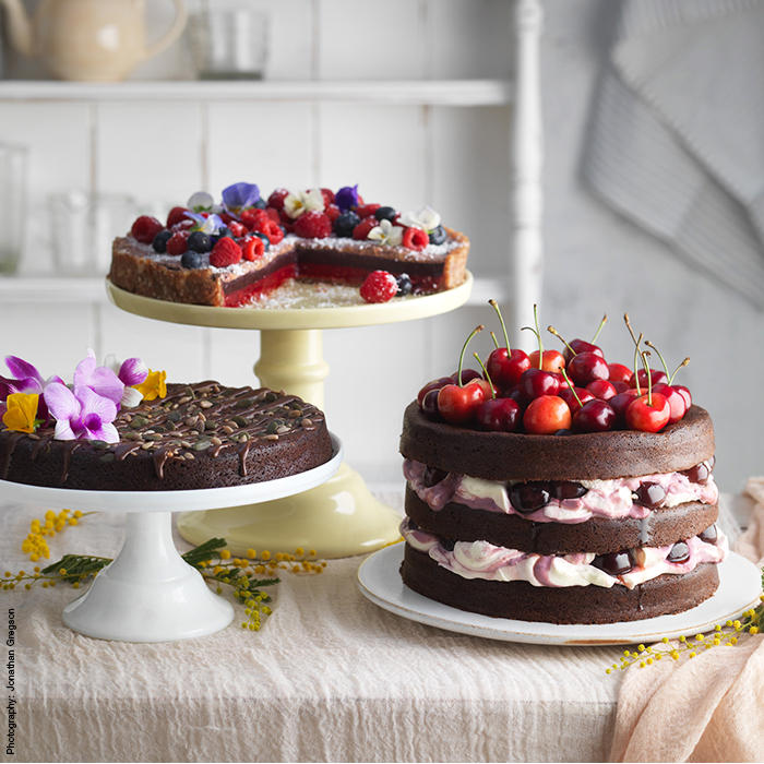 Vegan, gluten-free and dairy-free chocolate cakes decorated with fresh fruit and flowers