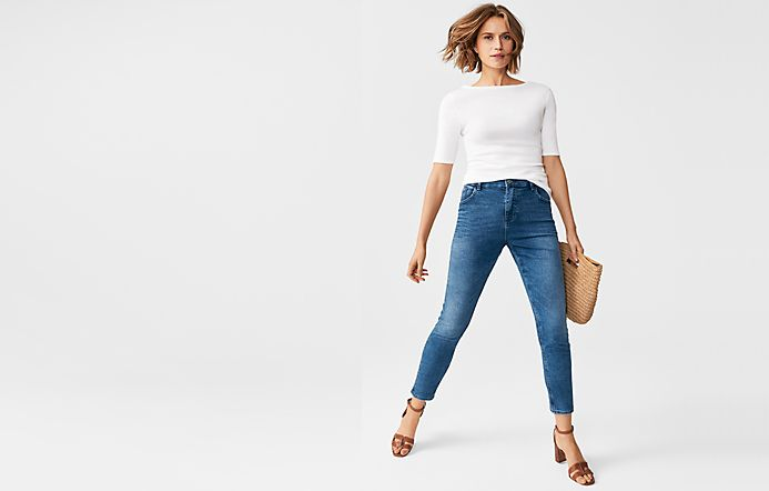 a2584c12f56c0 Woman wearing a white top, blue jeans, tan sandals and a straw bag