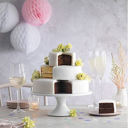 Three tiered wedding cake on a stand with glasses of champagne