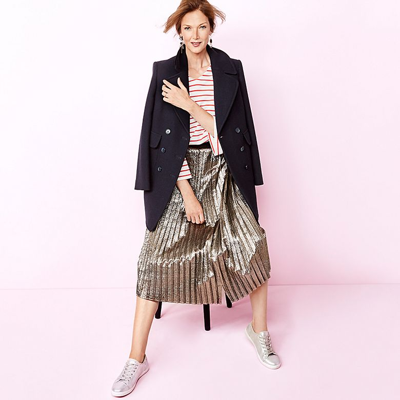 Model Rachel Boss wears Breton top, silver pleated skirt and metallic finish trainers