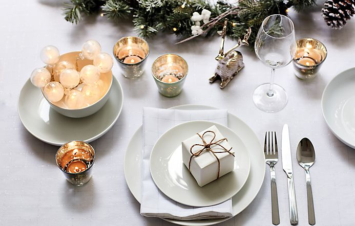 Dining table dressed with a white tablecloth, white crockery, cutlery and candles