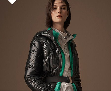 Model wears a black padded coat over a green padded jacket and grey ribbed jumper