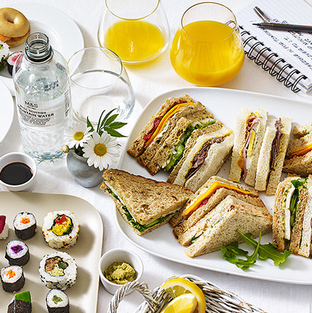 Lunch spread with sushi, mini bagels and sandwiches