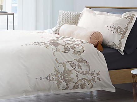 Patterned white bedding on a wooden bed