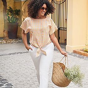 A woman wearing white linen trousers and peach checked shirt