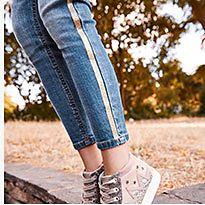 Girl wears blue jeans with a gold stripe and pink trainers