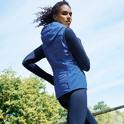 Woman running in a park wearing a blue body warmer, navy run top and navy leggings