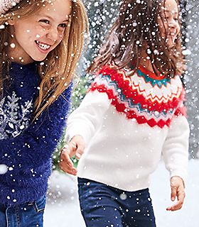 Girls playing in the snow wearing M&S jumpers