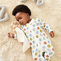 Baby wearing patterned sleepsuit