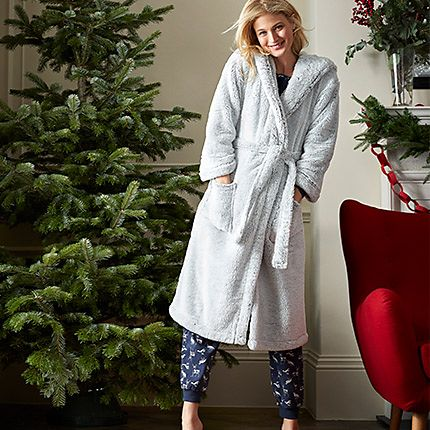 Woman stood by a Christmas tree wearing a fluffy dressing gown