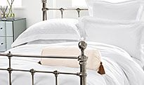 Plain white bedding on a metal bed
