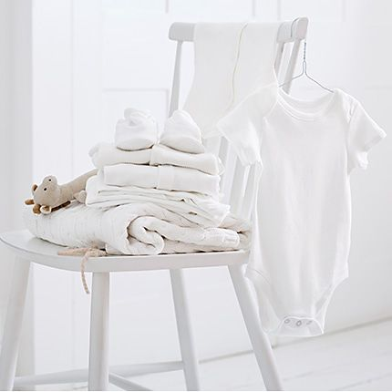 White chair with pile of white baby clothes