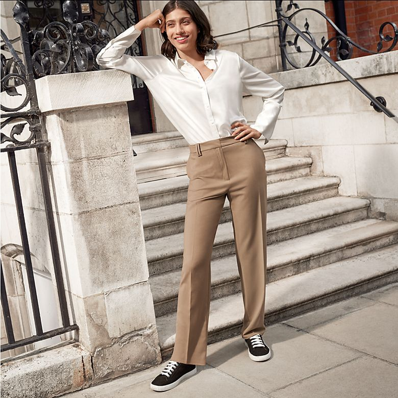 Woman wearing white shirt with camel tailored trousers