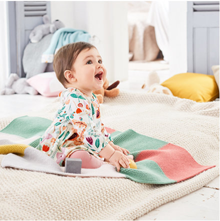 A baby girl lying on bed wearing M&S clothes