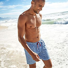 A man wearing swimming trunks on the beach