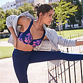 Woman stretching her leg on a railing wearing a patterned sports bra and leggings