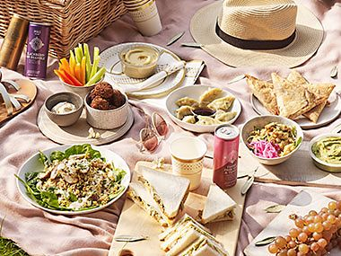 A picnic feast with sandwiches, salads, snacks, crudities and drinks