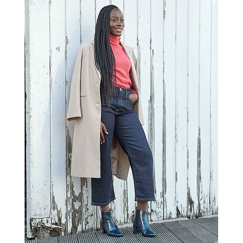 Woman wears coat, jeans and polo neck from Holly's Must-Haves collection