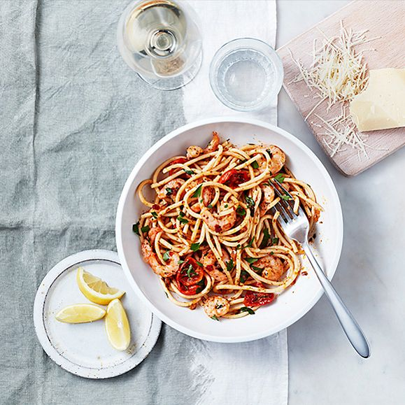 King prawn bucatini in a bowl with lemon wedges