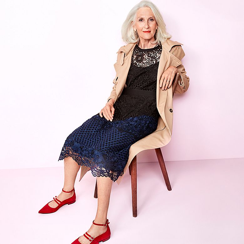 Model Sylviane wears trench coat, navy lace dress and red pointed shoes