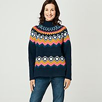 Woman wears a navy printed roll-neck jumper and blue jeans
